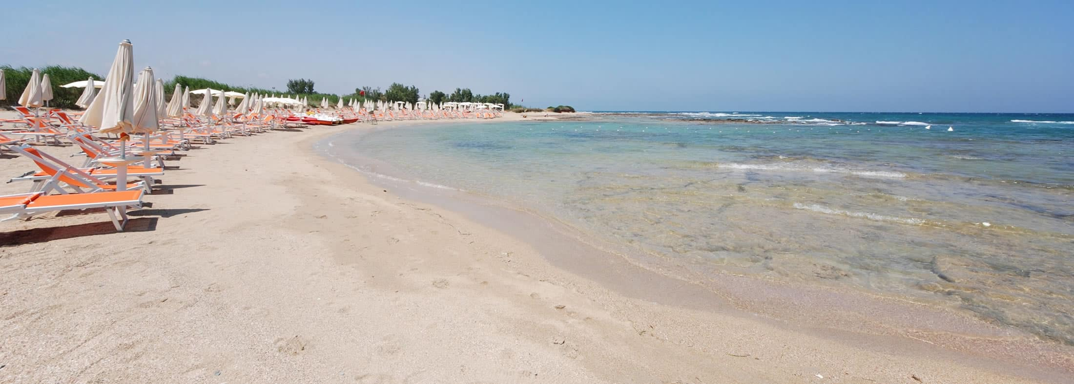 Mare e spiaggia con ombrelloni bianchi e lettini arancioni